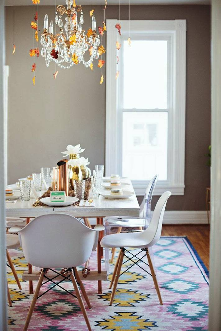белые пластиковые стулья за деревянным столом и хрустальная люстра в столовой