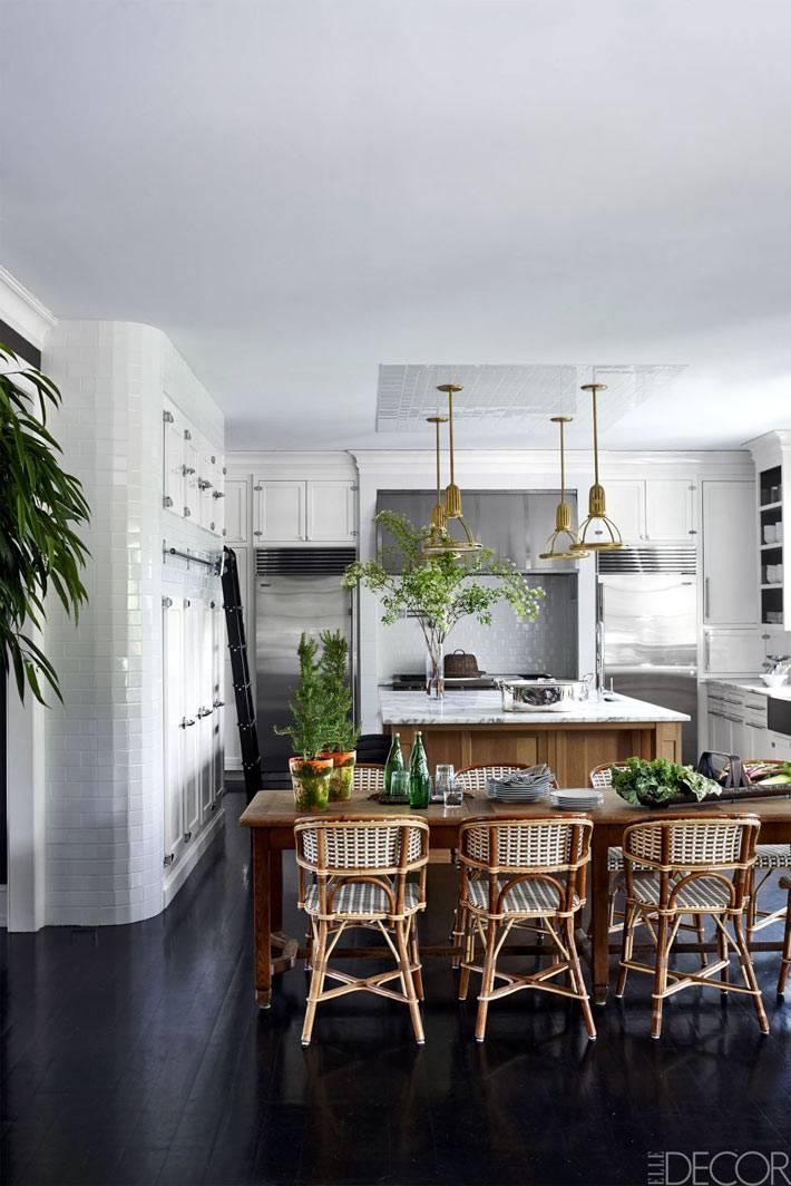 красивый дизайн кухни, совмещенной со столовой и плетеными стульями