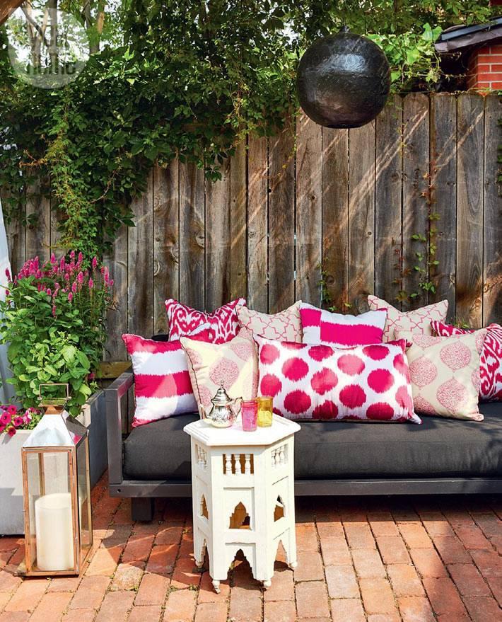 уютный внутренний двор с диваном и разноцветными подушками
