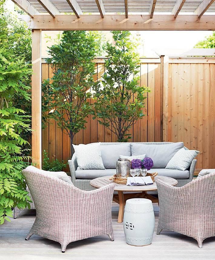 открытая терраса с плетеной мебелью и деревянной крышей