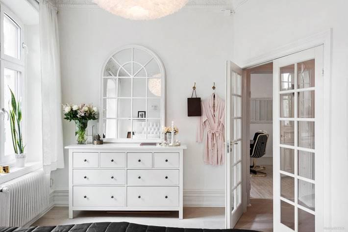 красивое зеркало на белом комоде в дизайне интерьера