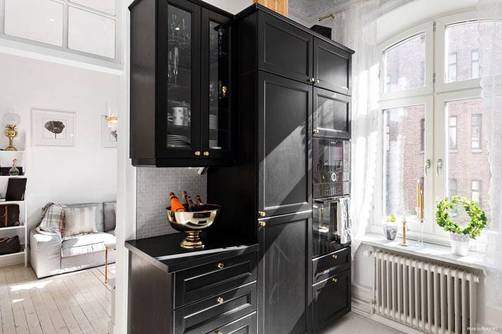контрастная черная кухни в абсолютно белом интерьере квартиры
