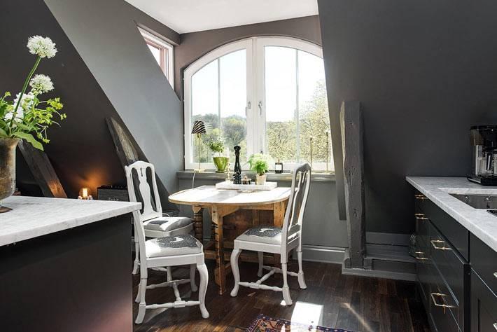 черные стены на кухне и обеденный стол возле небольшого окна