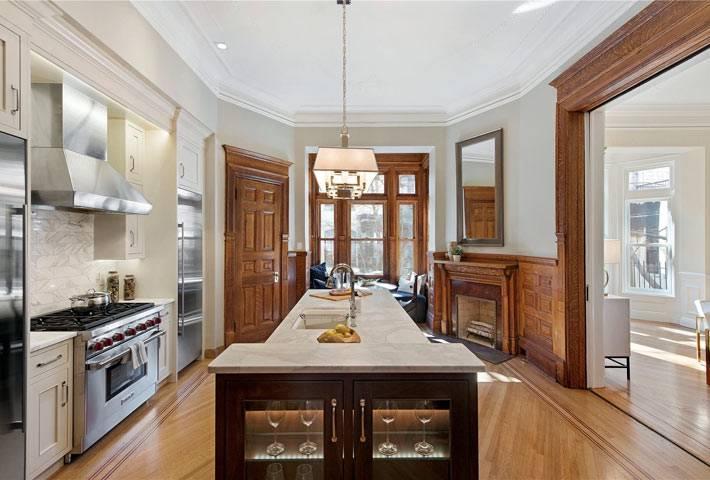 красивый интерьер кухни с отделкой из дерева и отсровом по центру
