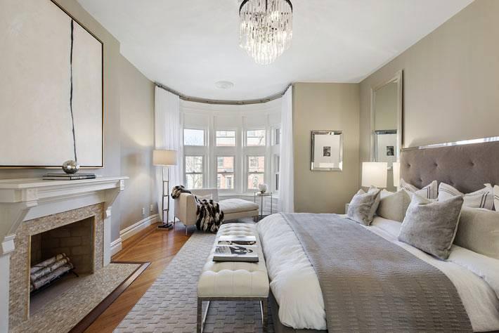 красивый дизайн интерьера спальни в бежевом цвете с камином