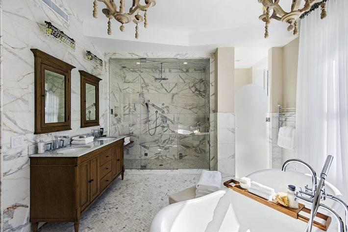 ванная на ножках в средине интерьера и деревянная тумба фото