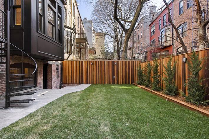 задний двор таунхауса с лужайкой и елочками фото