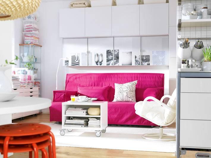 яркий розовый диван в белом интерьере кухни