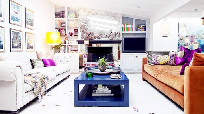 разноцветные диваны и синий журнальный стол в гостиной комнате