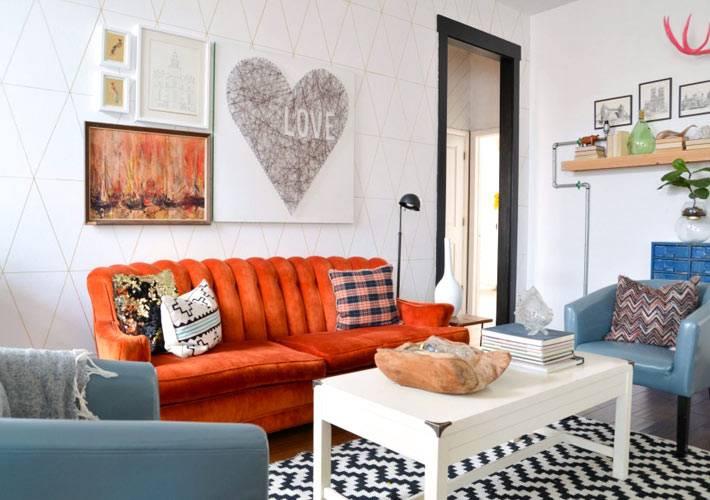 оранжевый диван и синие кресла в интерьере гостиной комнаты