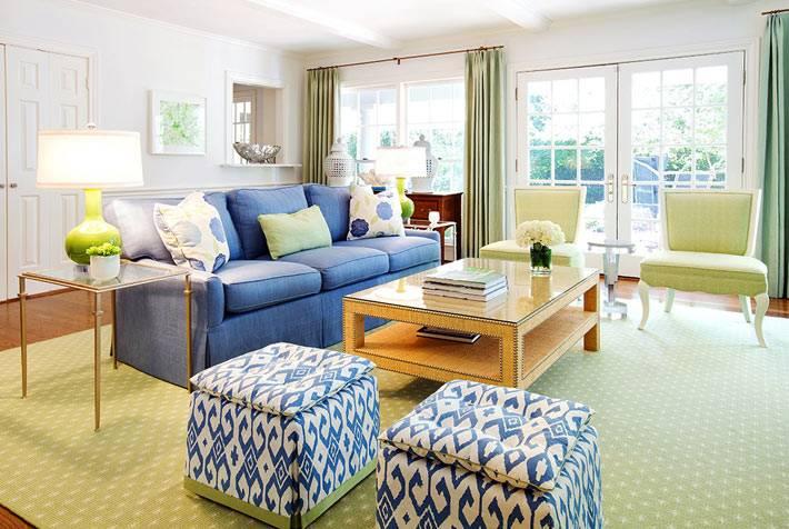 красивая гостиная комната с синим диваном и синими пуфами