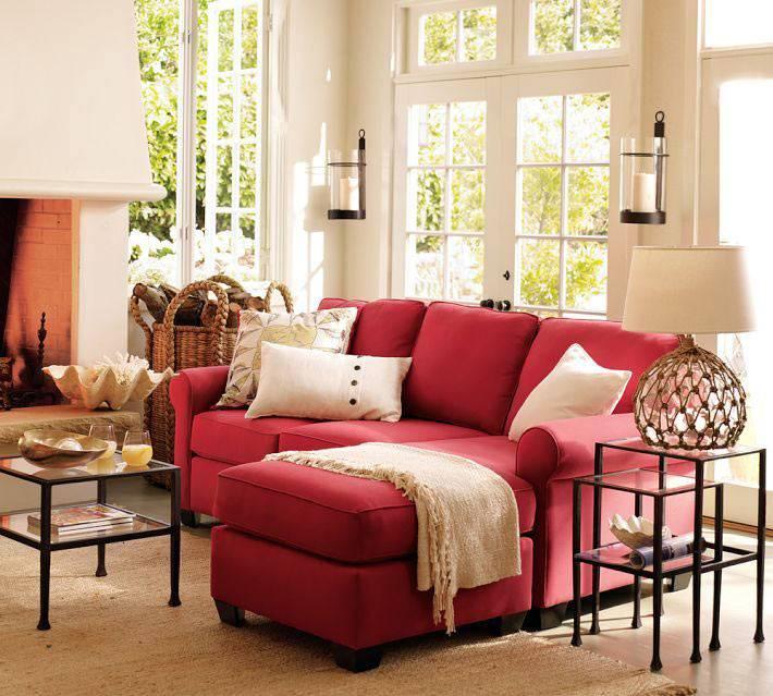 ярко красный угловой диван с белыми подушками в интерьере комнаты
