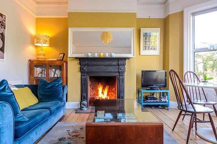 яркий интерьер гостиной: желтые стены и синий диван