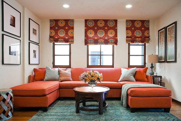 большой красный диван с красными римскими шторами на окнах