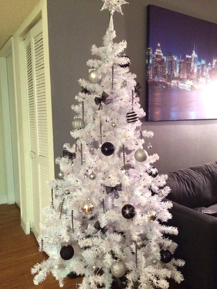белая искусственная елка в темном интерьере фото