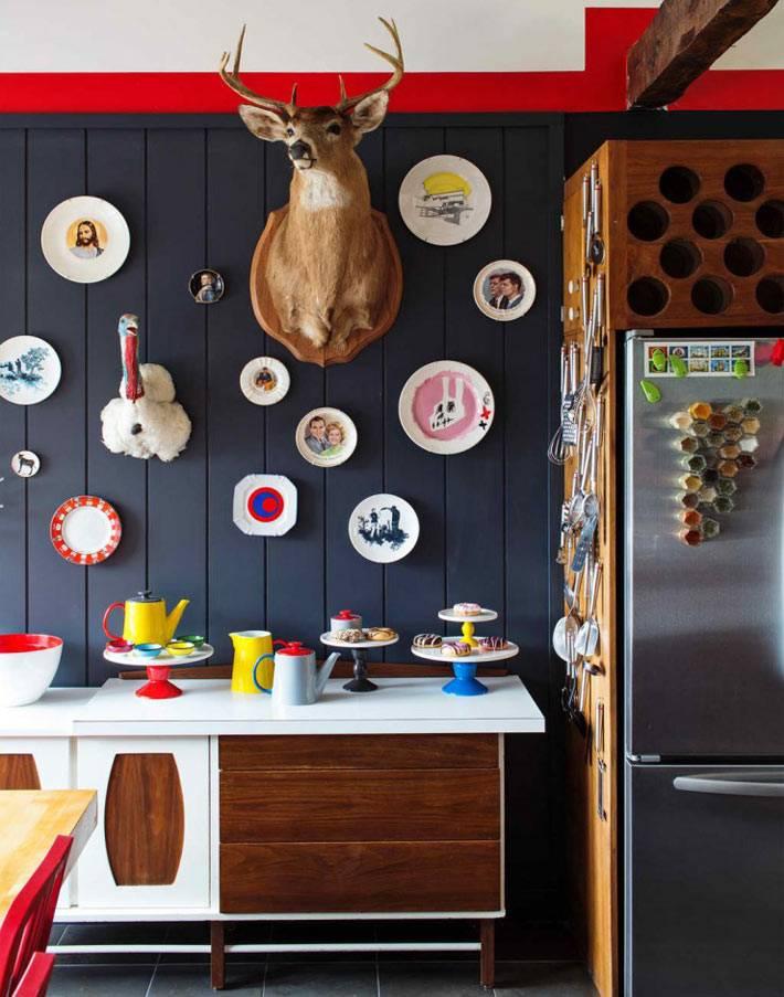 декоративные тарелки и голова оленя на черной стене кухни
