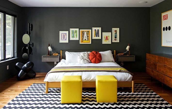 спальная комната с темными стенами и желтыми пуфами