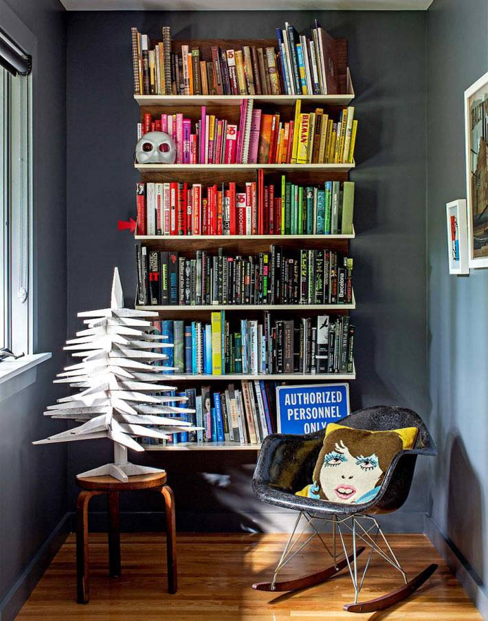 уютный уголок для чтения возле полок с домашней библиотекой