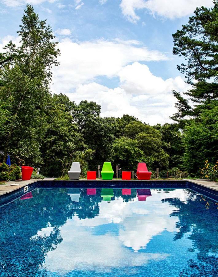большой бассейн с яркими стульями и шезлонгами фото