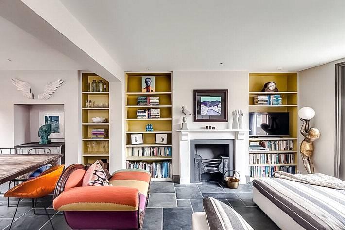 неординарный дизайн интерьера гостиной с ярким диваном