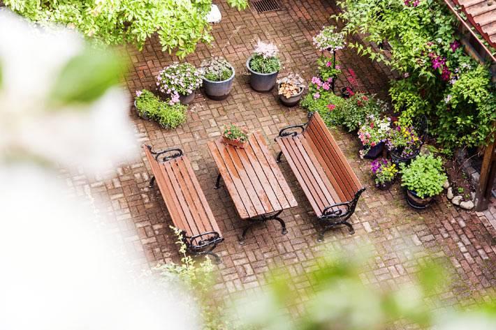 уютный двор с деревянными лавочками и столом