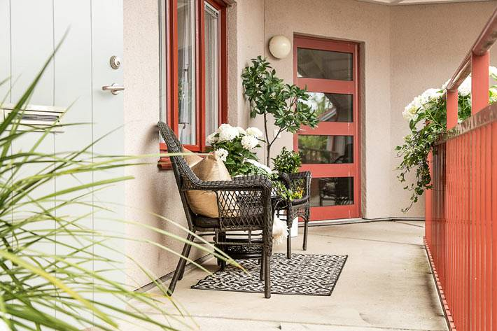 общий балкон с плетеной мебелью и ковриком