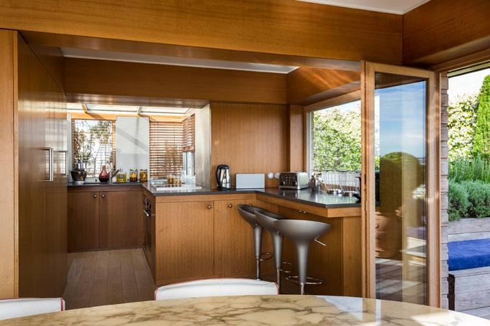 интерьер кухни с отделкой из дерева и деревянной мебелью