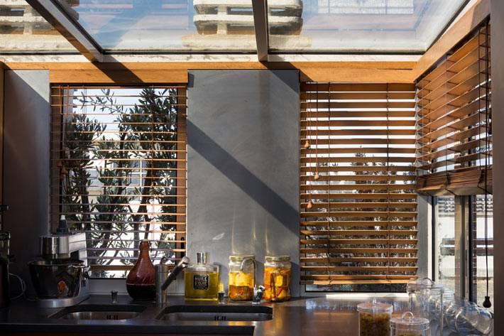 деревянные жалюзи на окнах в кухне со стеклянным потолком