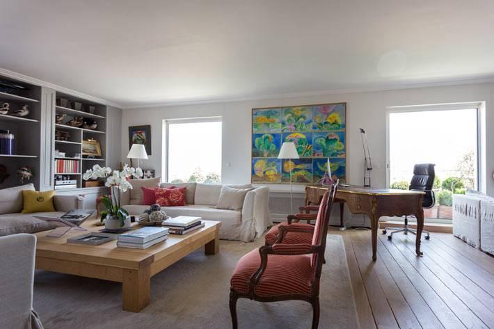 большая гостиная с белыми диванами и большим квадратным столом