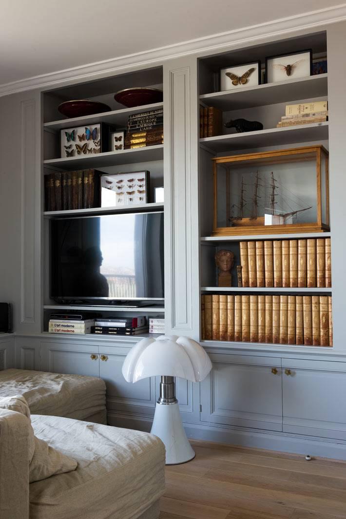 стеллаж под телевизор и книги в интерьере гостиной комнаты