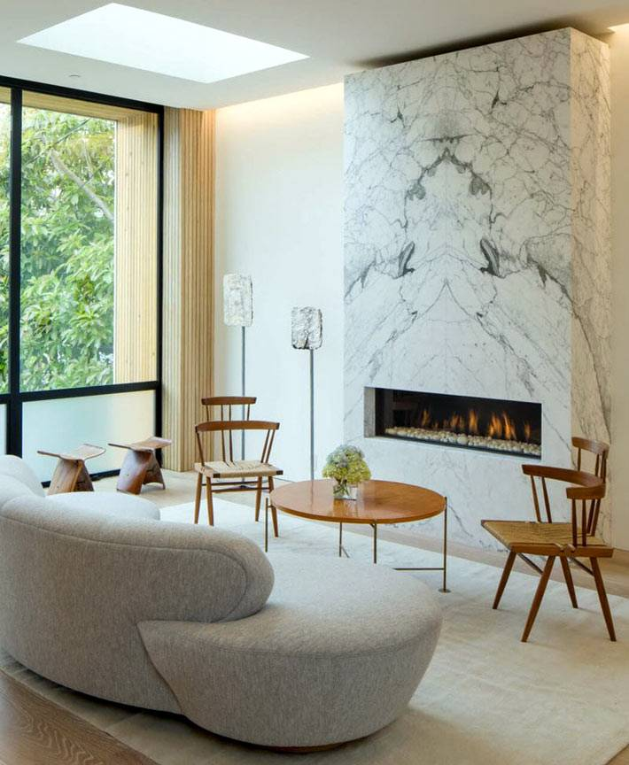 мраморная стена вокруг камина в комнате с панорамными окнами