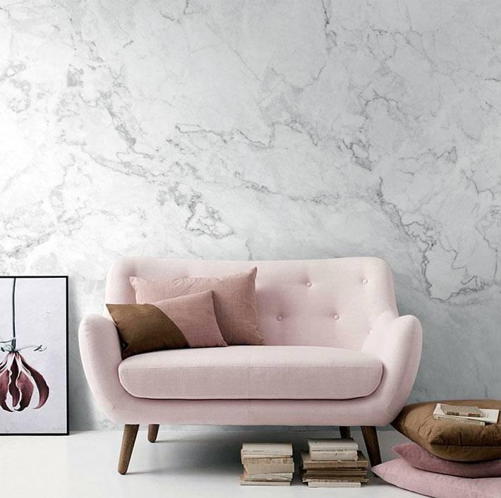 мраморная акцентная стена в комнате с розовым диваном