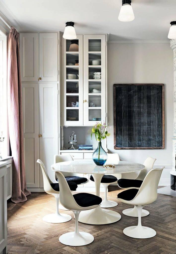 круглый обеденный стол и меловая доска на кухне фото