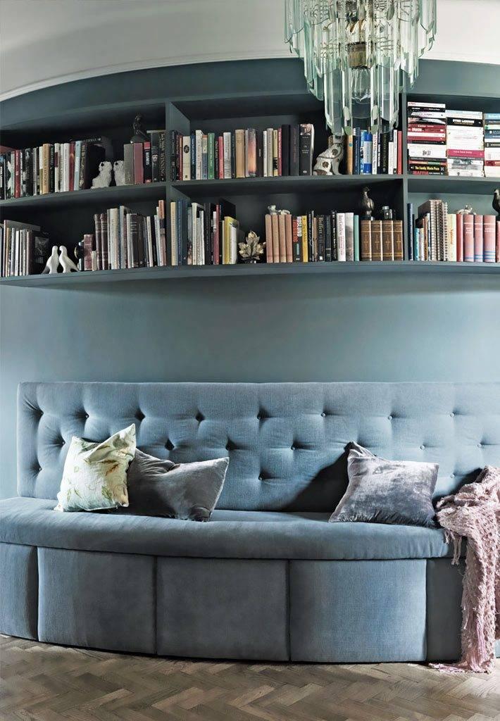 полки с книгами и диван на фоне насыщенных стен