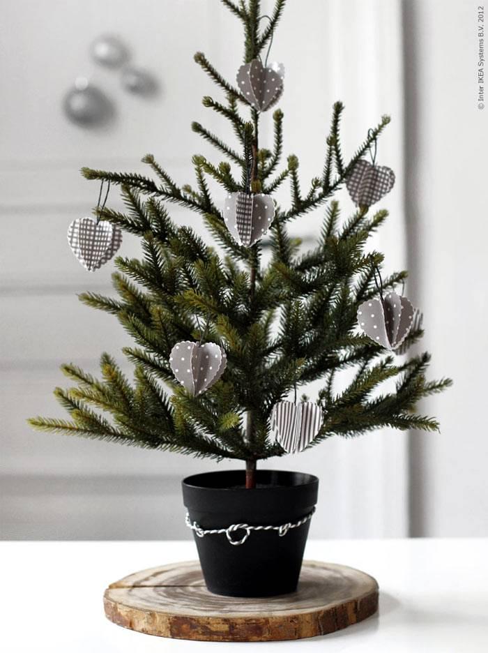 маленькая елочка в черном горшке с самодельными украшениями фото