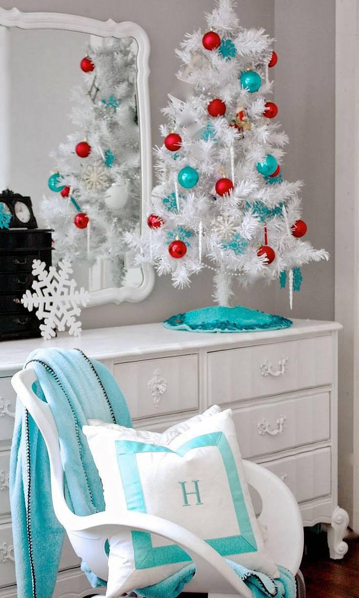 маленькая белая елка с голубыми и красными шарами в комнате