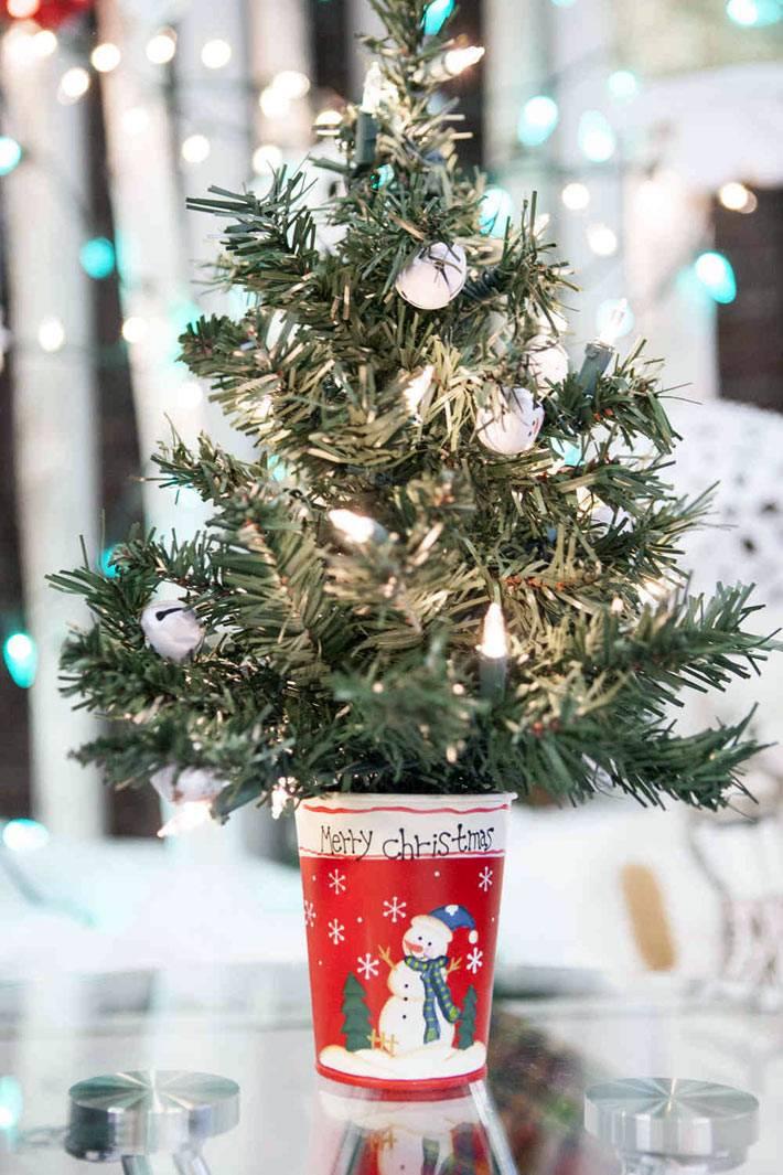 новогодняя мини-елка в красном стакане на столе