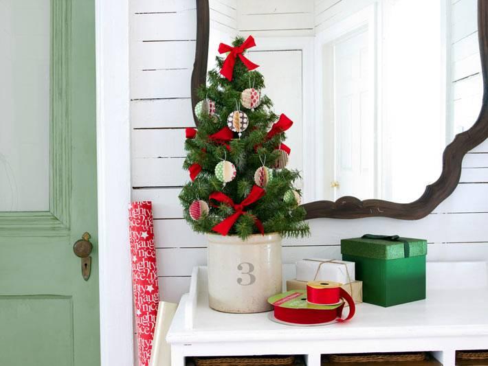 маленькая новогодняя елка с красными бантами на столе