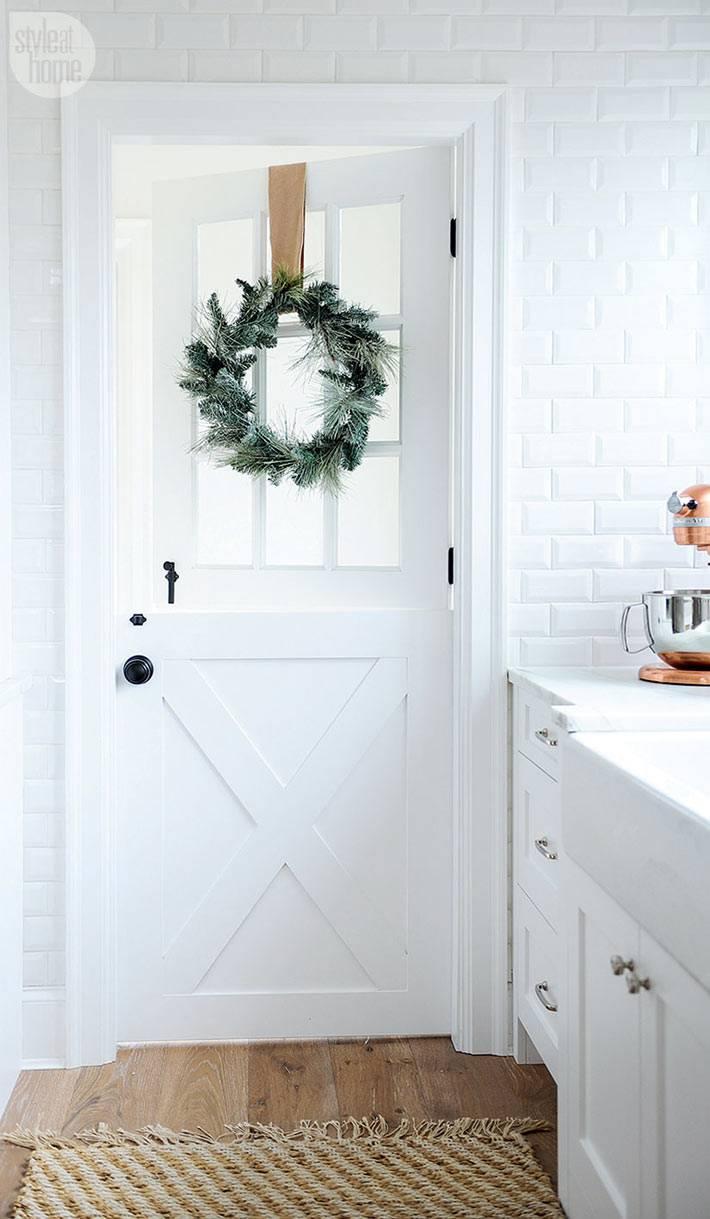 новогодний венок на белой двери в кухне фото