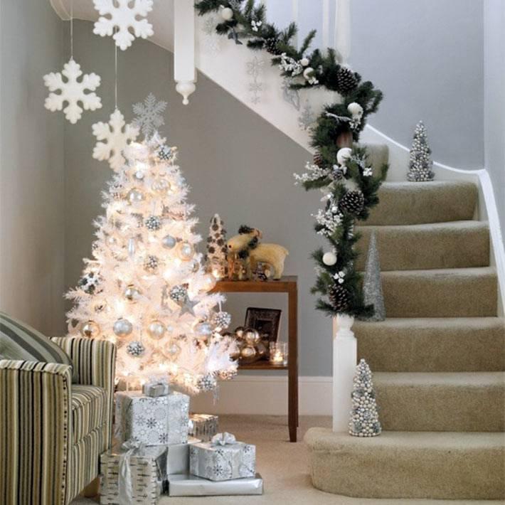 белая елка, серебристые новогодние украшения возле ступеней в доме