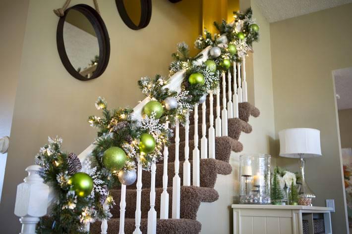 зеленые шары и ветки ели украшают перила ступеней лестницы фото