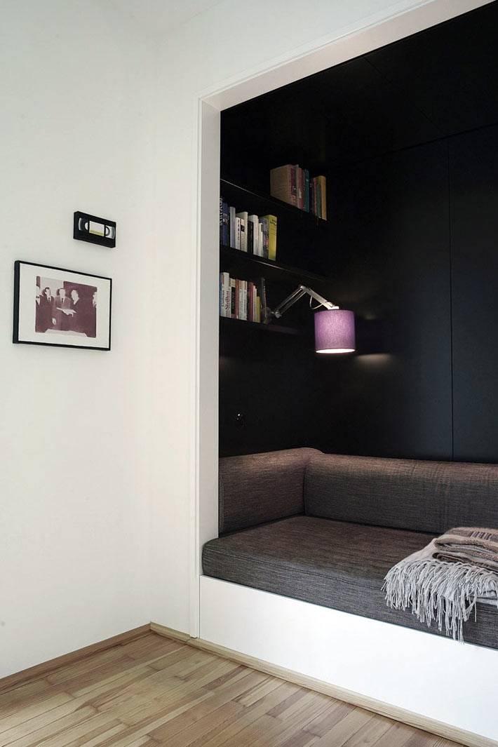 уютная ниша с черными стенами и диваном для чтения
