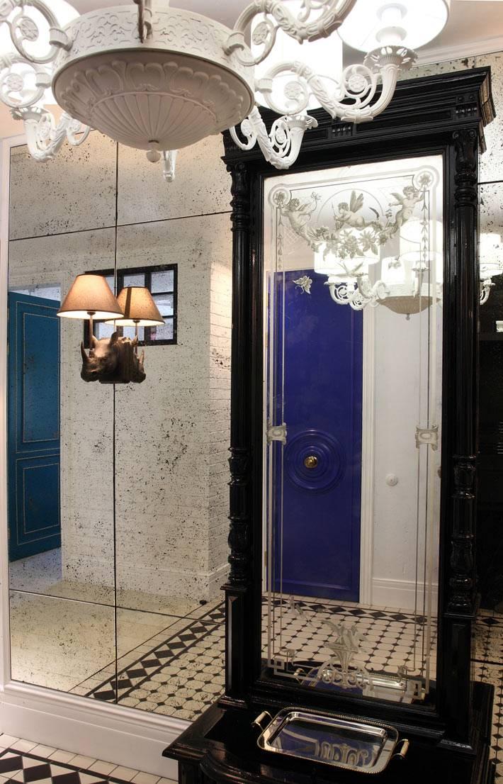 красивое большое зеркало в черной раме в коридоре квартиры