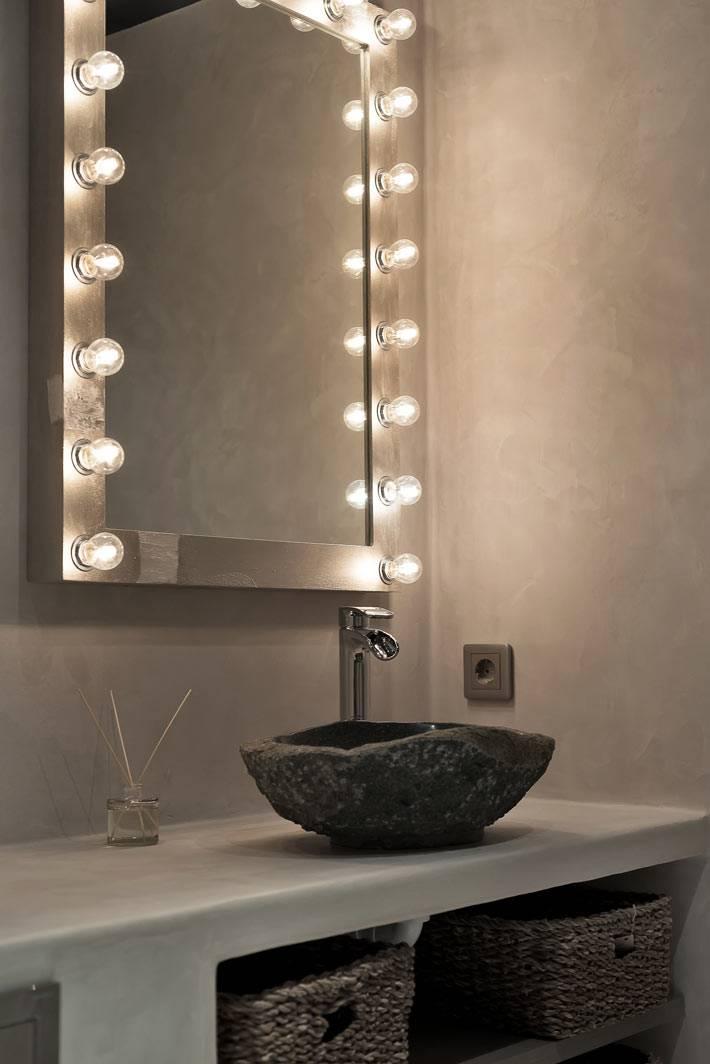 Умывальник из камня и зеркало с лампочками в ванной комнате