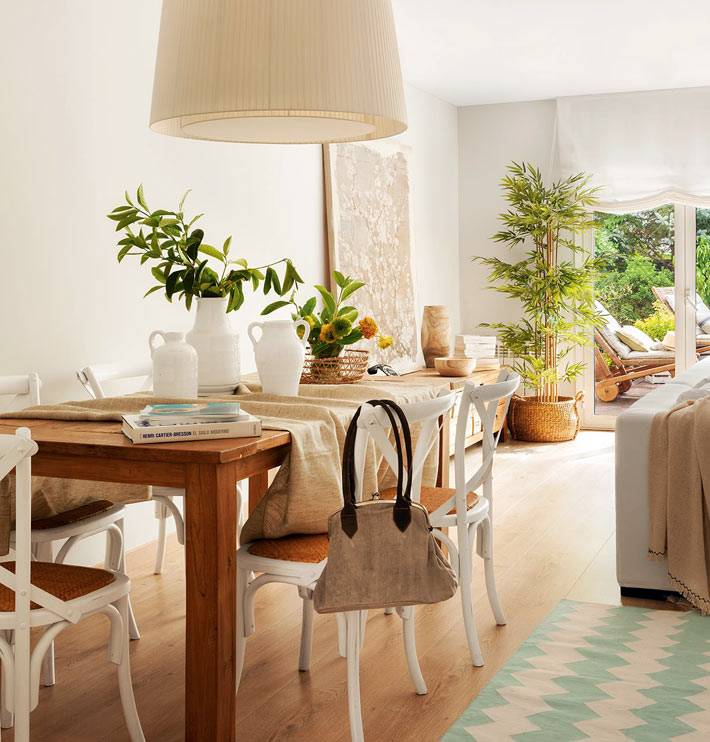 деревянный обеденный стол с белыми стульями и абажуром