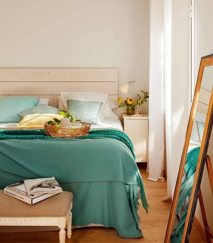 бирюзовые цвета и напольное деревянное зеркало в спальне