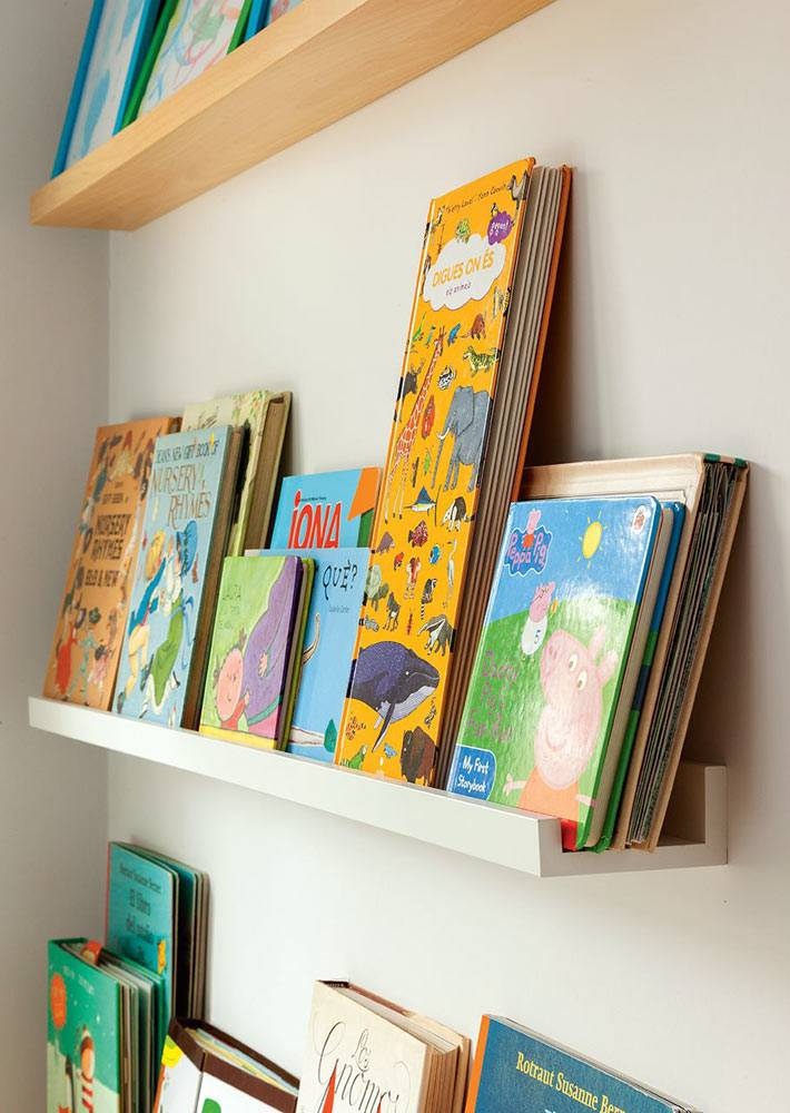 детские книги на узких полках на стене детской комнаты