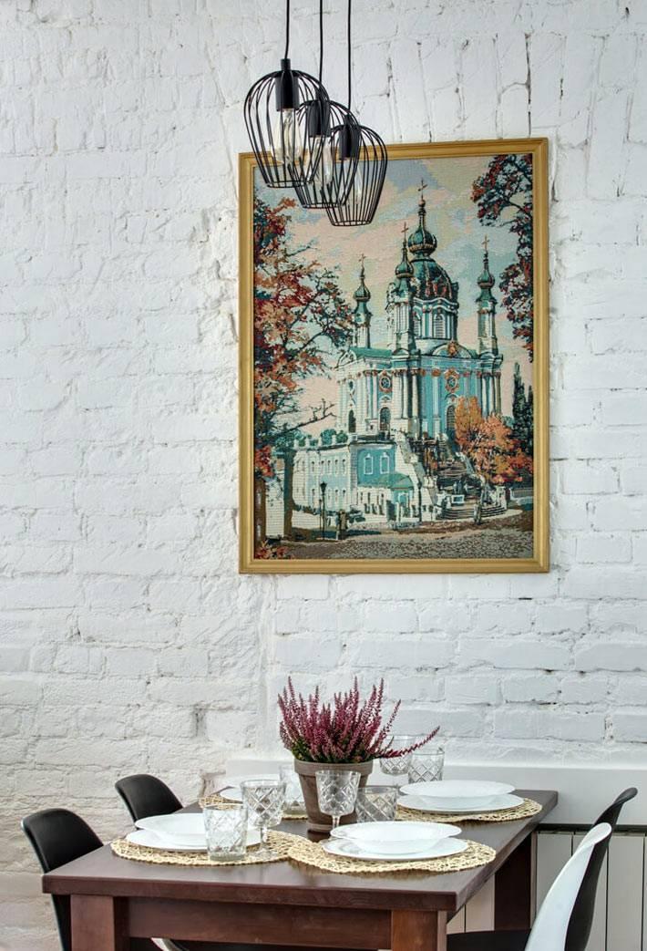 обеденный уголок с подвесными лампами и вышитой картиной