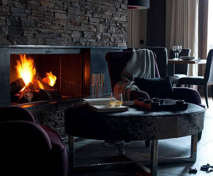 уютный камин с живым огнем в зимнем интерьере дома