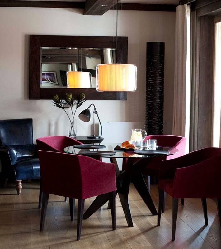 Обеденная зона со стеклянным столом и красными креслами фото